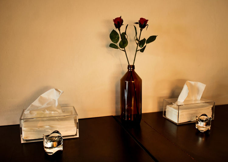 Close-up of roses in vase on table against wall