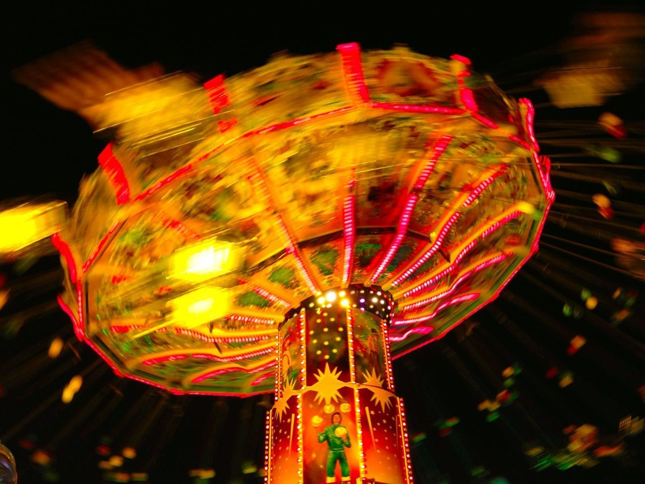 Blurred motion of illuminated chain swing ride at night