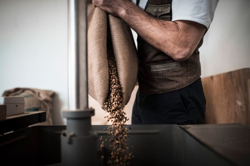 Midsection of man pouring coffee beans in coffee roaster