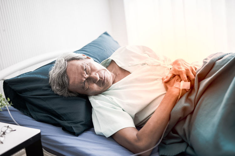 High angle view of senior male patient with stomachache on bed in hospital