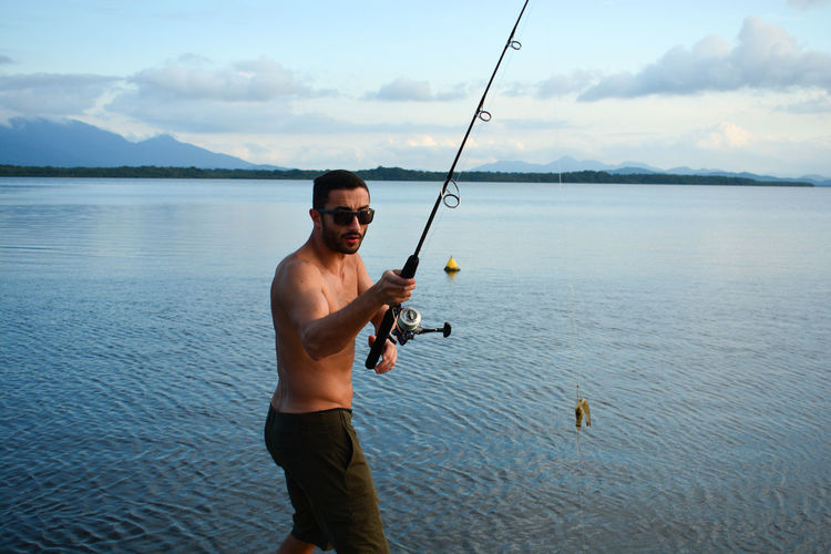 Portrait of young man holding fishing rod while standing in lake against sky