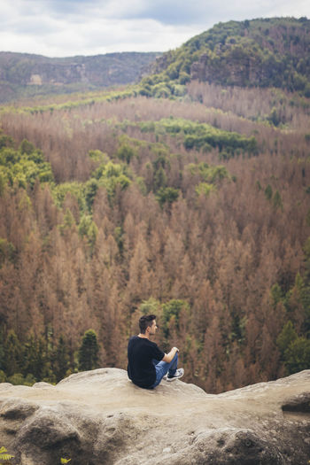 Man sitting on mountain looking at mountains