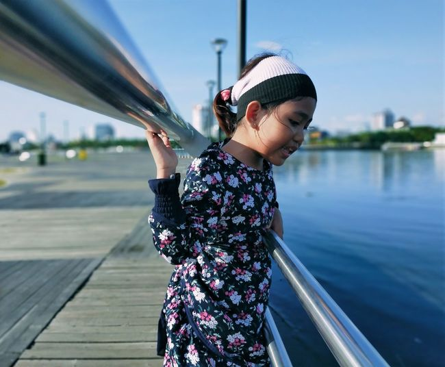 Young woman standing by railing