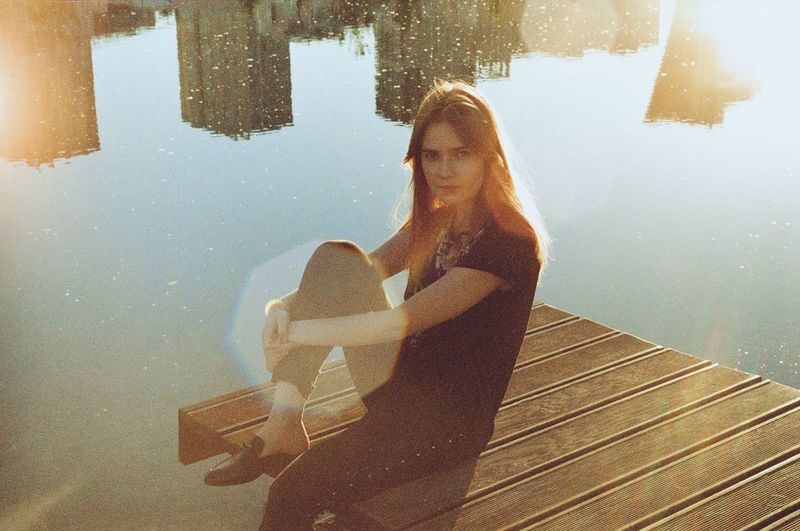 Portrait of young woman sitting by lake on jetty
