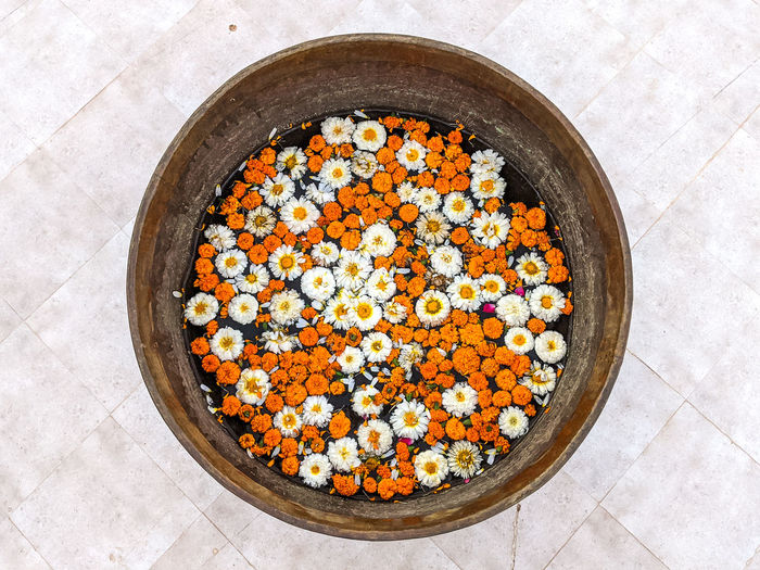 High angle view of flower heads swimming in large bowl on floor