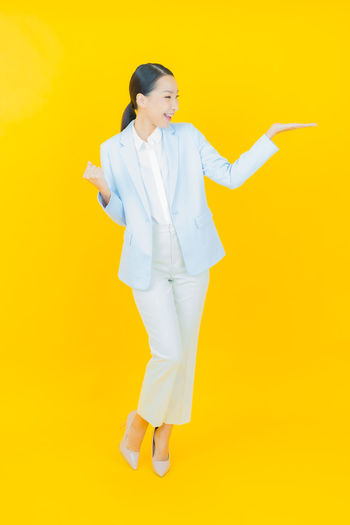 Woman standing against yellow background