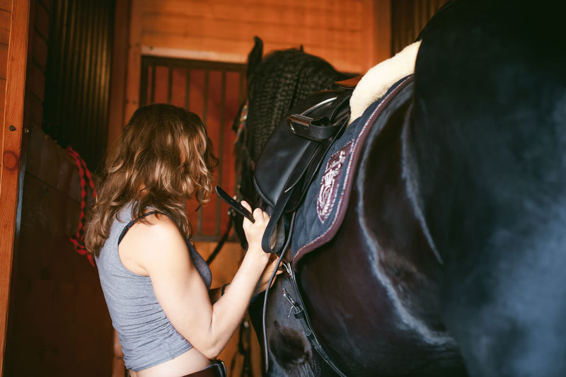 Side view of young woman adjusting horse bridle at stable