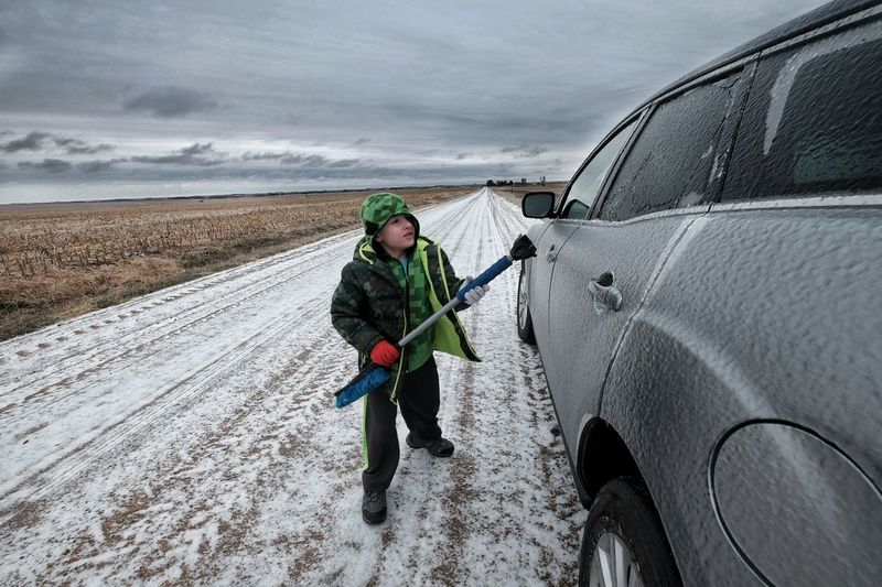 Boy Cleaning Car During Winter