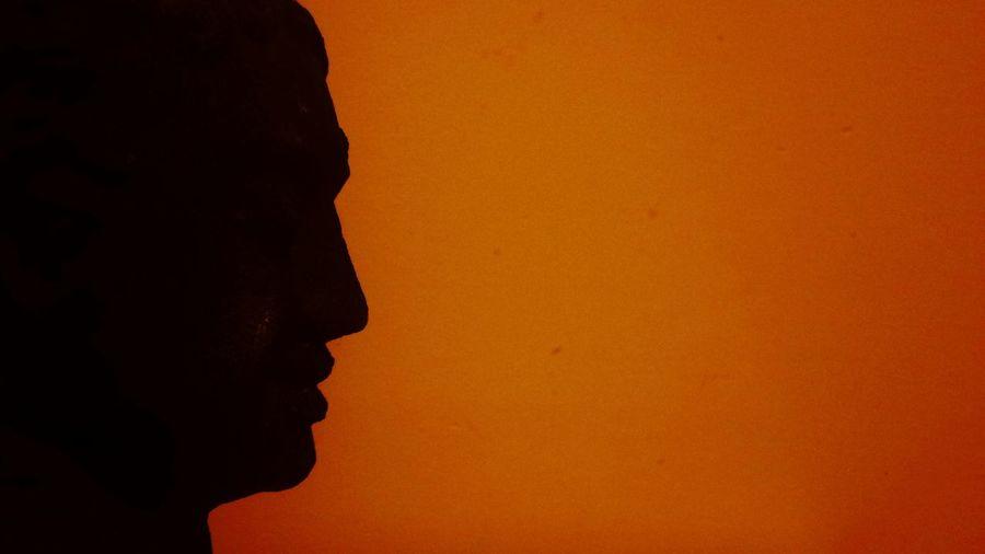 Silhouette statue against orange sky during sunset