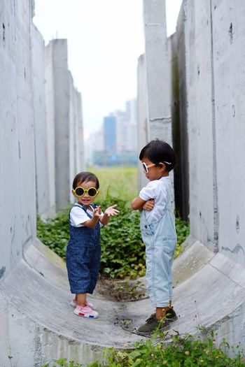 Siblings Wearing Sunglasses While Standing By Walls