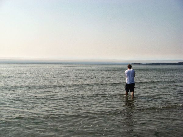 One lone man standing in body of water Loneliness Lonely Thinking Adult Adults Only Beach Clear Sky Full Length Horizon Over Water Man Standing Men Nature One Man Only One Person Outdoors People Person In Water Rear View Scenics Sea Standing Sunset Tranquil Scene Vacations Water
