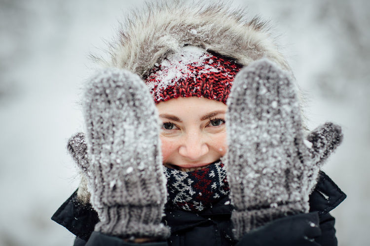 Portrait of smiling woman wearing gloves during winter