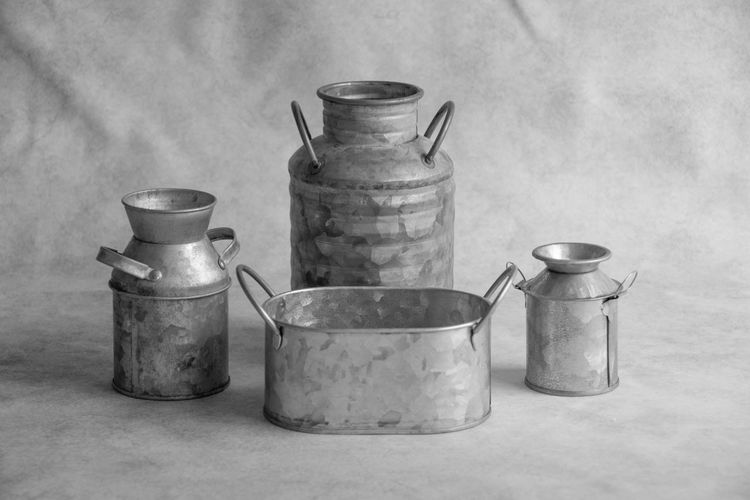 Four vintage tin milk containers in black and white. Container Indoors  Kitchen Utensil No People Still Life Household Equipment Jar Food And Drink Metal Group Of Objects Kitchen High Angle View Close-up Large Group Of Objects Steel Alloy