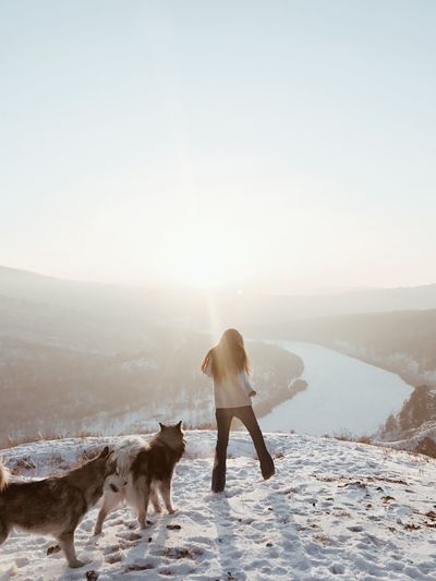 Rear view of woman with dog standing on snow