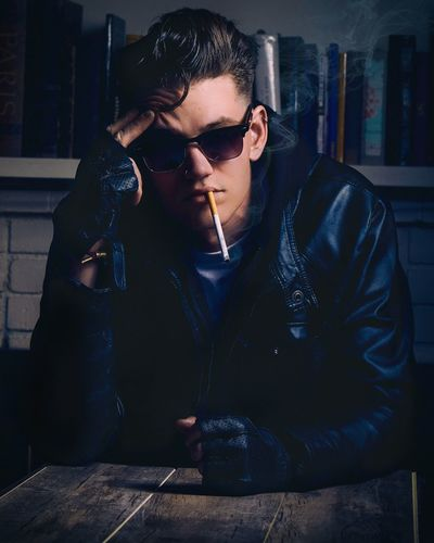 A thought and a smoke. People Young Adult Portrait Indoors  Lifestyles Real People One Person James Dean Greaser Rockabilly RockandRoll Vintage Handsome Man Jawline Sunglasses Badass Cool Portrait Photography Portrait Of America Portrait Of A Man  Smoke Cigarette  Guys The Portraitist - 2017 EyeEm Awards