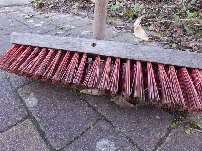 A street broom with rough red long bristles and wooden handle Broom Stick Handle Wooden Red Color Bristles Outdoors No People Day Outside Garden Photography Garden Tools Housekeeping Cleaning Cleaning Equipment Object Broomstick Brush Dirty