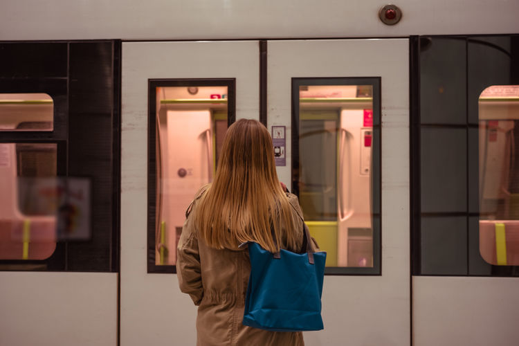 Rear View Of Young Woman Waiting For Subway. Train. Real People Rear View One Person Women Hairstyle Standing Lifestyles Hair Adult Leisure Activity Long Hair Casual Clothing Indoors  Architecture Three Quarter Length Waist Up Bag Store Entrance SPAIN Subway Passenger Tourist Wagon Doors