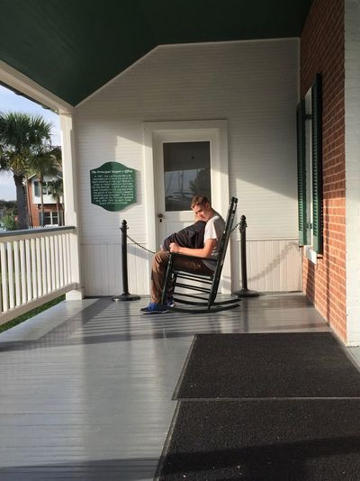 Side view of brothers sitting on rocking chair against house