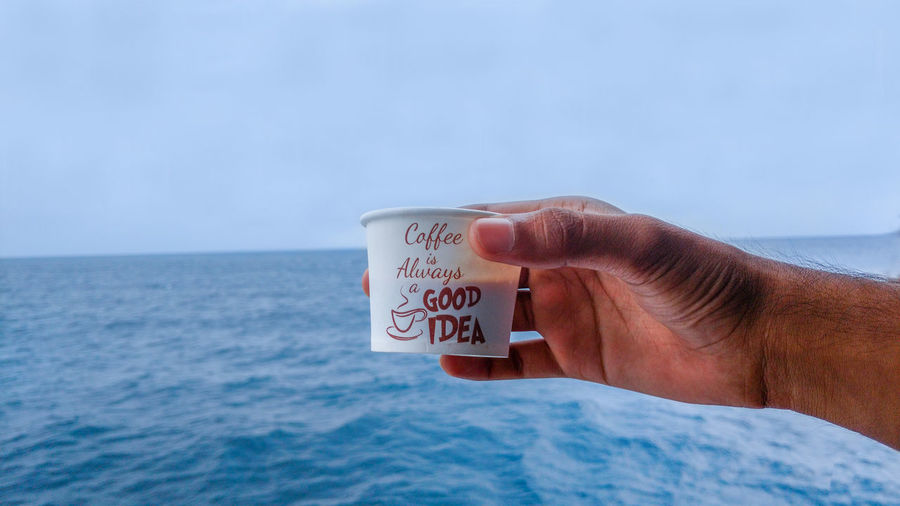 Close-up of hand holding coffee and tea by sea against sky. man enjoying coffee and tea