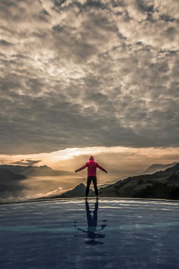 Man Standing At Infinity Pool Against Cloudy Sky During Sunset