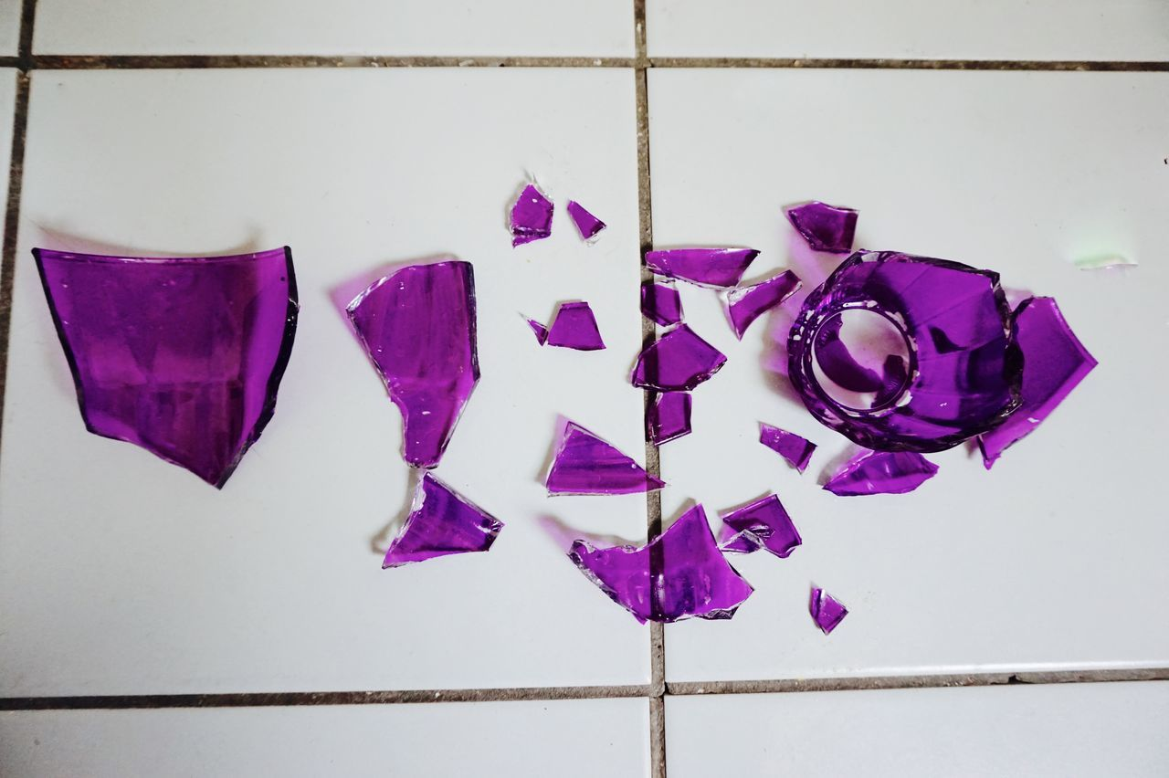 High Angle View Of Damaged Glass Decoration On Tiled Floor