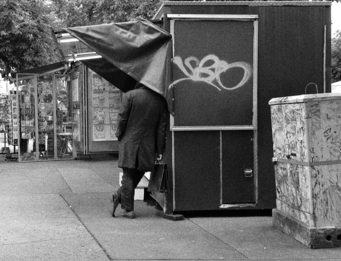 Rear view of man leaning on stall