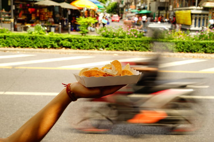 Close-up of hand holding nacho chips in plate against blurred motorcycle