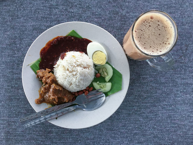 Coconut Milk Rice Or Locally In Malaysia Known As Nasi Lemak With Spicy Sauce, Hard Boiled Egg, Cucumber And Meat Rendang With Milk Tea. Nasi Lemak Is A Famous Breakfast Set Amongst Malaysian. Malaysia Truly Asia Malaysian Food Nasi Lemak Teh Tarik Close-up Day Directly Above Drink Food Food And Drink Freshness Healthy Eating Indoors  Indulgence Meat No People Plate Ready-to-eat Refreshment Serving Size Table Temptation