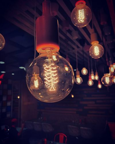 Low angle view of illuminated light bulb at night