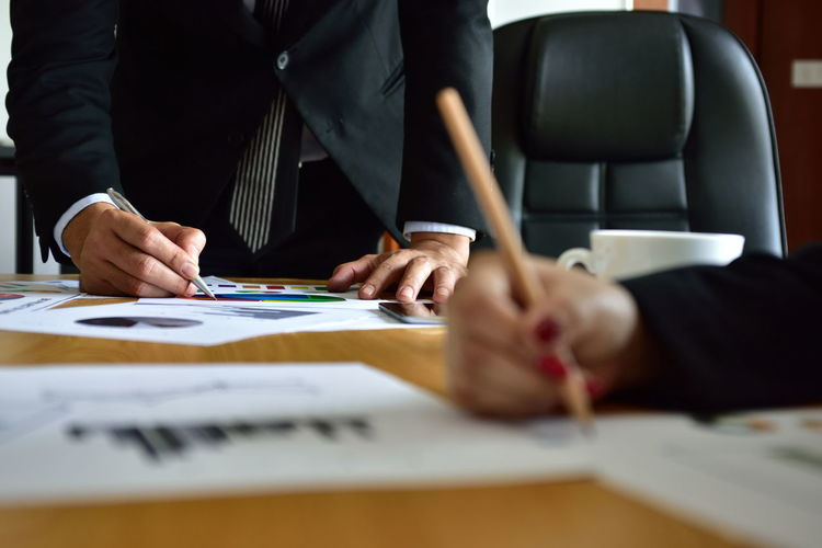 Cropped image of business colleagues working on table