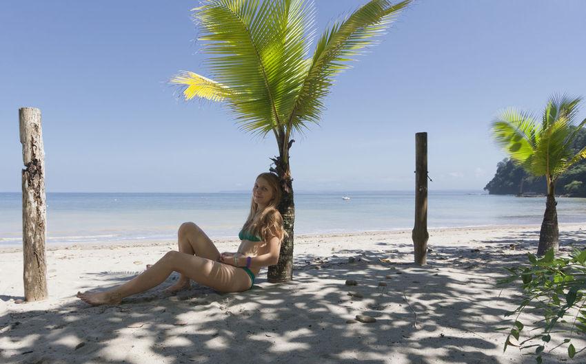 Portrait of mid adult woman in bikini sitting by palm tree at beach
