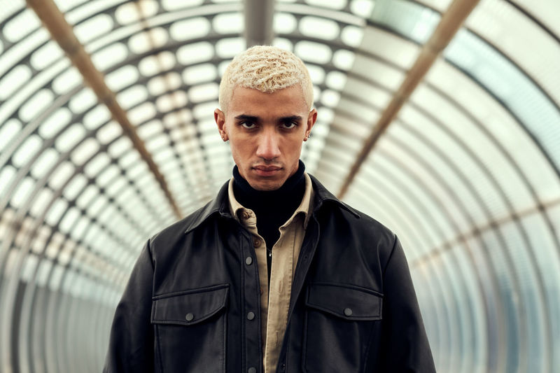Portrait of young man with blond hair standing in tunnel
