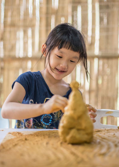 Close-up of girl making craft with mud on table