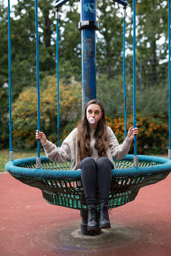 Young woman blowing bubble while sitting on outdoor play equipment