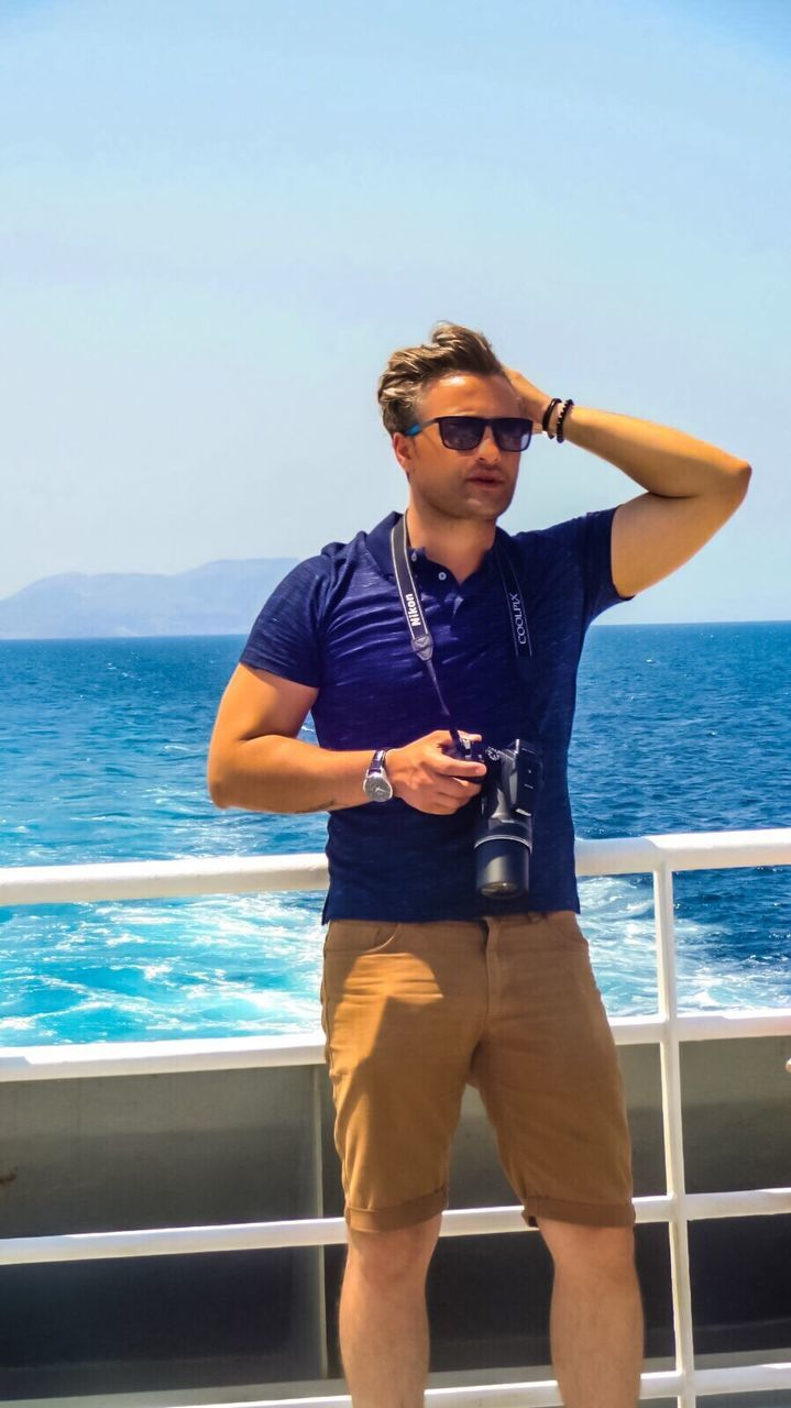 sunglasses, sea, one person, real people, young adult, water, front view, young men, standing, leisure activity, lifestyles, horizon over water, outdoors, sky, nature, beauty in nature, day, full length, nautical vessel