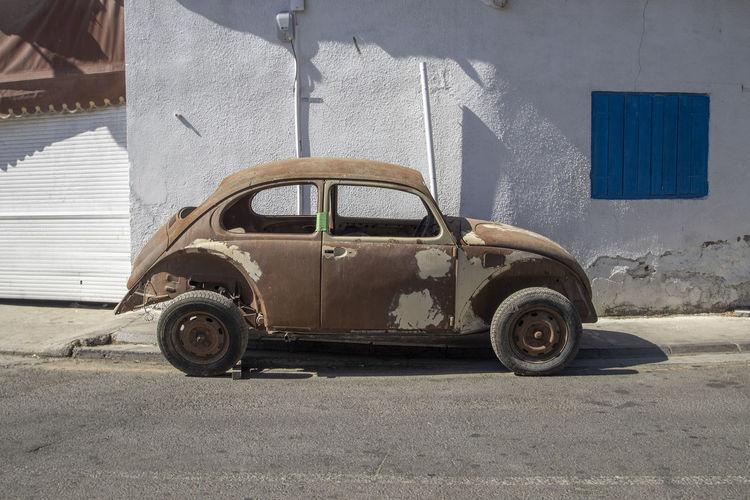 Vintage car on road against buildings in city