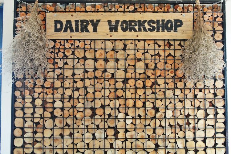 Dairy workshop text on metal grate against stack of firewood