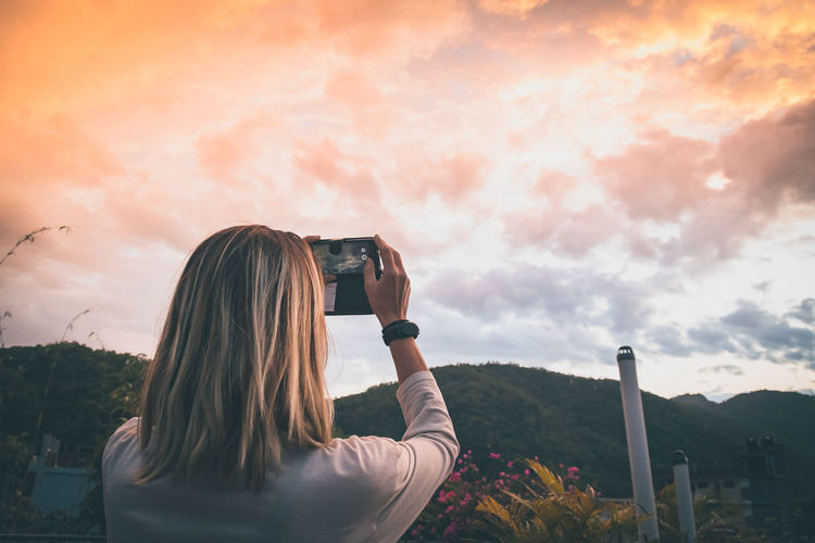 Rear view of woman photographing against sky during sunset