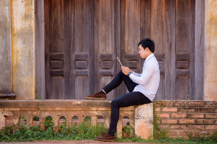 Side View Of Young Man Using Digital Tablet While Sitting On Retaining Wall Against Building