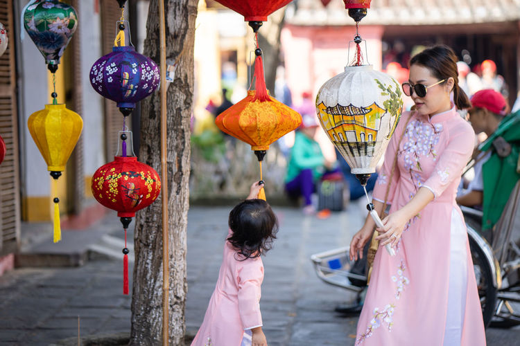Mother and daughter looking at paper lamp at market in hoi an.