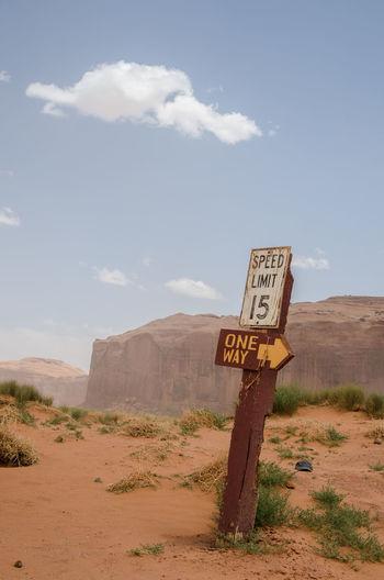 Information sign on sand against sky