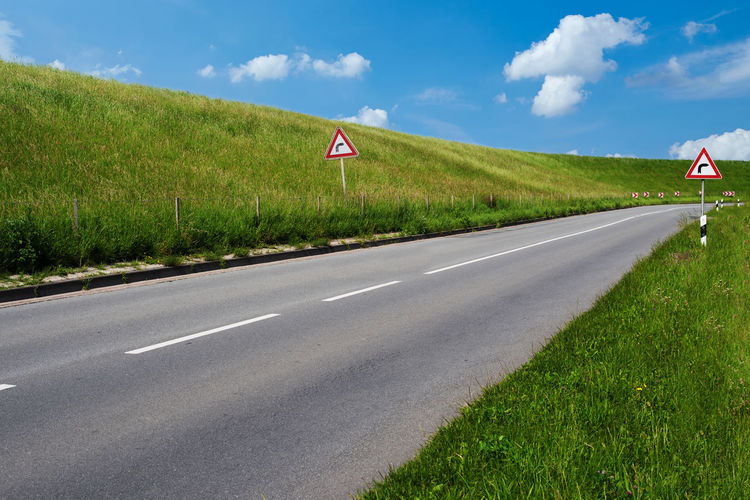Beauty In Nature Bending Cloud - Sky Curve Day Dike Embankment Grass Green Color Growth Landscape Nature No People Outdoors Road Road Sign Scenics Sky The Way Forward Tranquil Scene Tranquility Transportation Tree