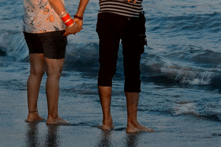 Low section of couple holding hands while standing on shore at beach