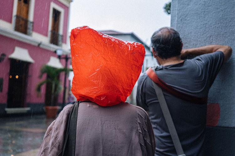 Rear view of people on street in rain