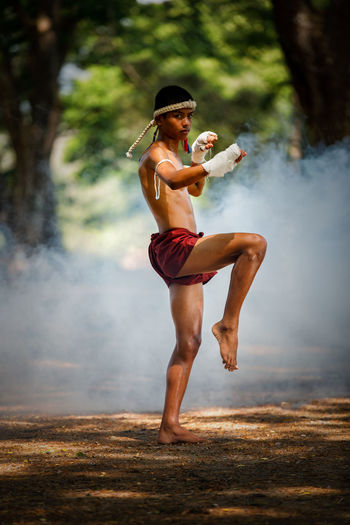 Full length of shirtless warrior standing on one leg in forest