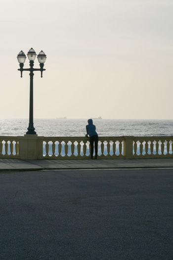 young women looking at the atlantic ocean in porto. portugal Looking Watching Sunset Distance Clear Sky Sea Full Length Beach Silhouette Water Street Light Standing Sky