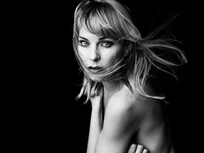 Portrait of shirtless female model over black background