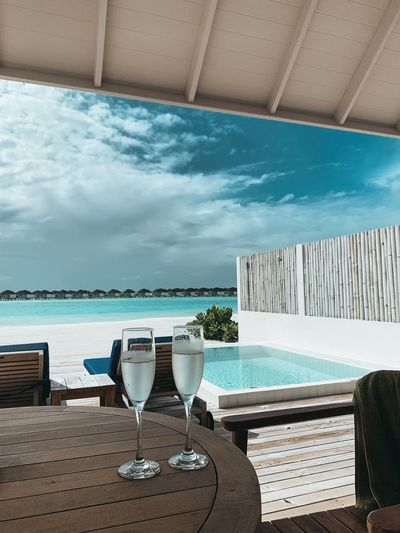 Chairs and tables by swimming pool against sky