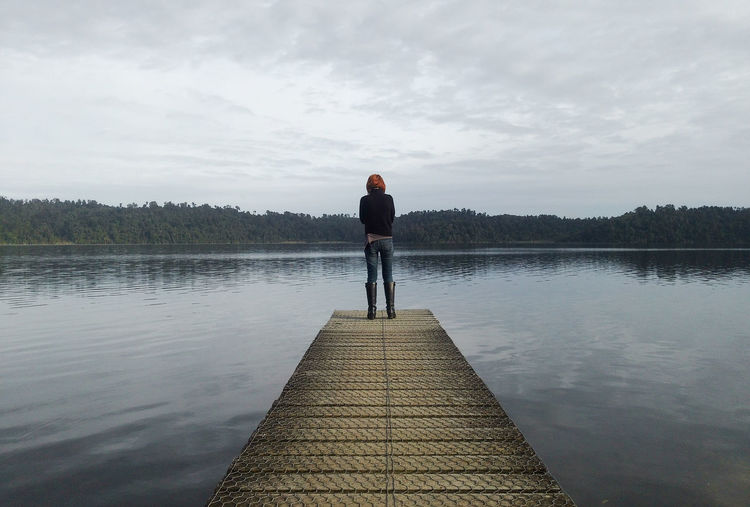 Rear view of woman standing on pier by lake against sky