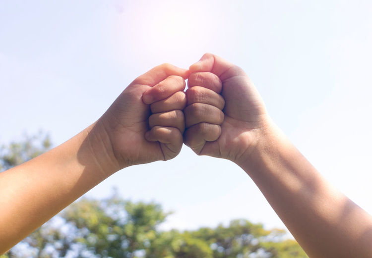 Close-up of hands fist bumping against sky